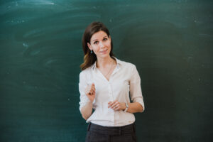 Woman pointing finger at blank board. School teacher pointing the finger at a blank board. Student stands at the blackboard. Business woman presenting the idea to the board. Girl in the school.